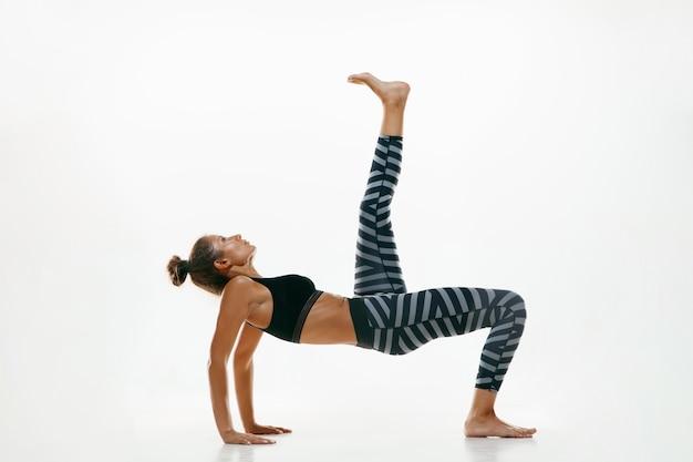 고립 된 요가 연습을 하 고 스포티 한 젊은 여자. 유연한 여성 모델 연습에 적합합니다. 건강한 생활 습관과 신체와 정신 발달 사이의 자연스러운 균형의 개념. 무료 사진