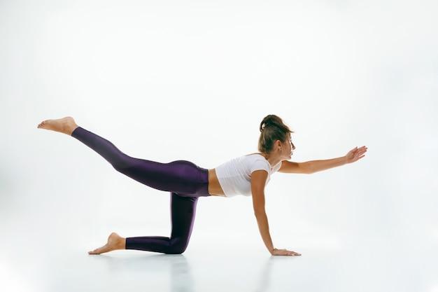 흰색 공간에 고립 된 요가 연습을 하 고 스포티 한 젊은 여자. 유연한 여성 모델 연습 적합 무료 사진