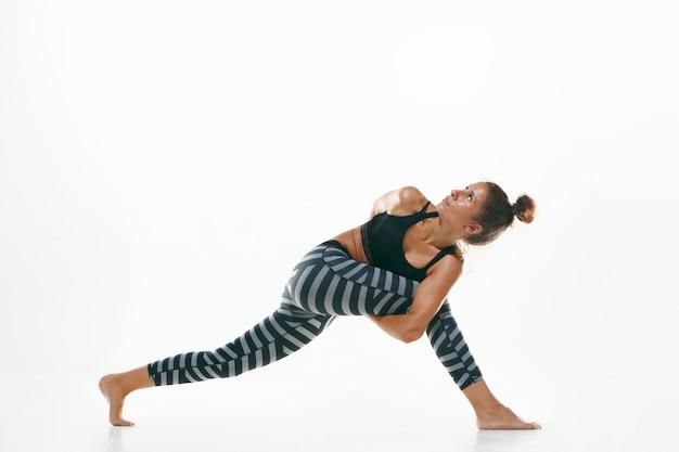 흰색 스튜디오 배경에 고립 된 요가 연습을 하 고 스포티 한 젊은 여자. 유연한 여성 모델 연습에 적합합니다. 건강한 생활 습관과 신체와 정신 발달 사이의 자연스러운 균형의 개념. 무료 사진