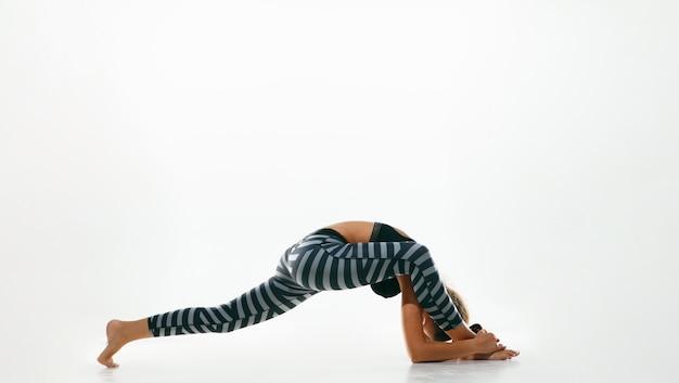 Giovane donna sportiva che fa pratica di yoga isolata su spazio bianco. fit modello femminile flessibile che pratica Foto Gratuite