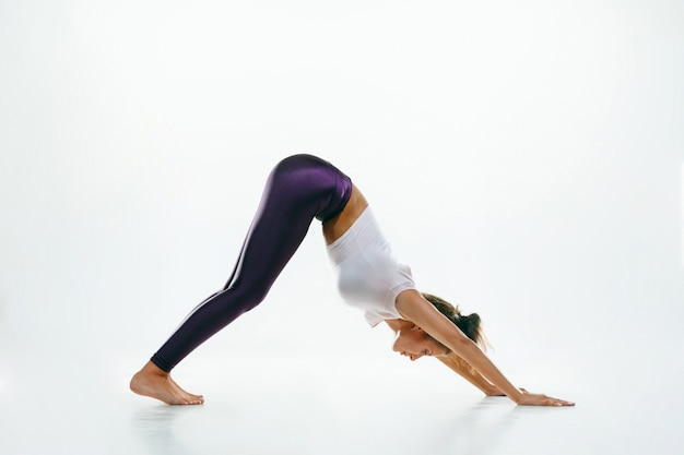 Giovane donna sportiva che fa pratica yoga isolata su sfondo bianco studio. fit modello femminile flessibile che pratica. concetto di stile di vita sano e equilibrio naturale tra corpo e sviluppo mentale. Foto Gratuite
