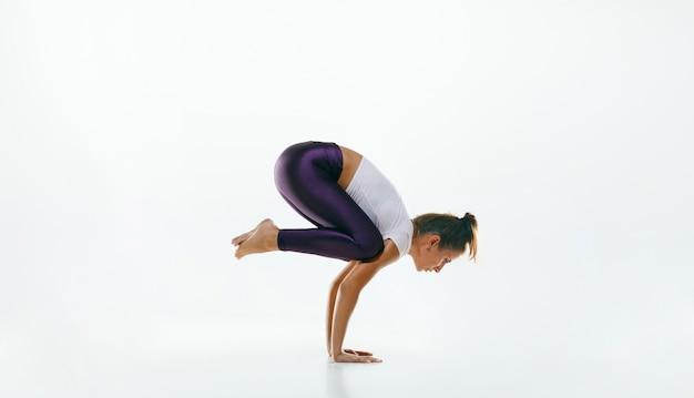 Giovane donna sportiva che fa pratica di yoga isolata su bianco Foto Gratuite