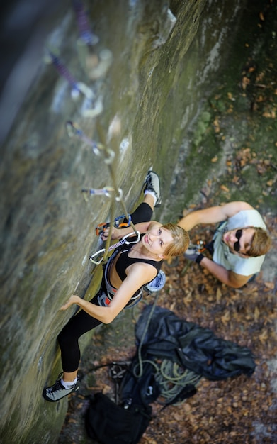 Sporty young woman rock climbing with carbines and rope Premium Photo