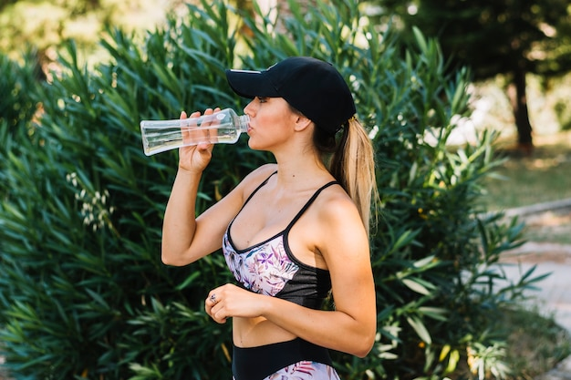 Sporty young woman standing near the plants drinking water from bottle Free Photo