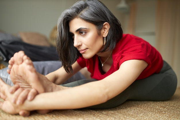Спортивная молодая женщина с седыми волосами, практикующая хатха-йогу дома, делая пасчимоттанасану Бесплатные Фотографии