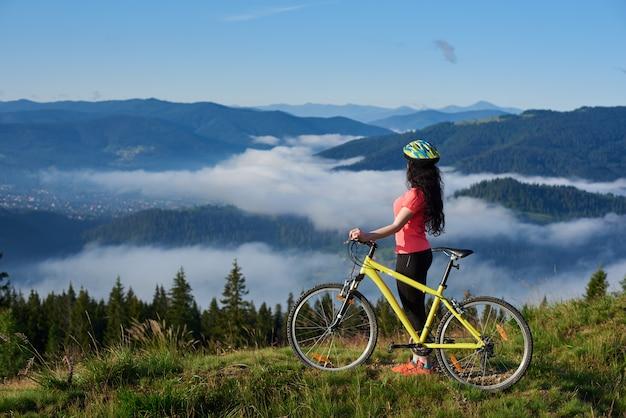 Взгляд со стороны sporty женского велосипедиста с желтым велосипедом в горах, в утре. туманные горы, леса на размытом фоне Premium Фотографии