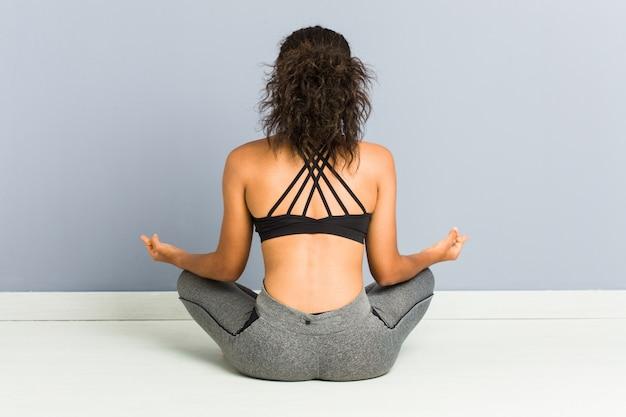 Йога молодой афро-американской sporty женщины сидя практикуя Premium Фотографии