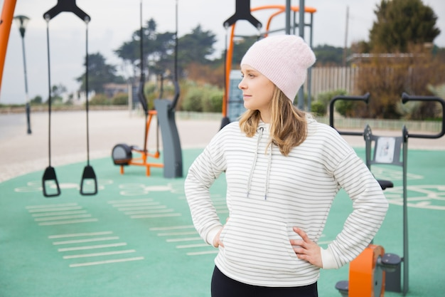 Задумчивый sporty женщина готова для тренировки на открытом воздухе Бесплатные Фотографии