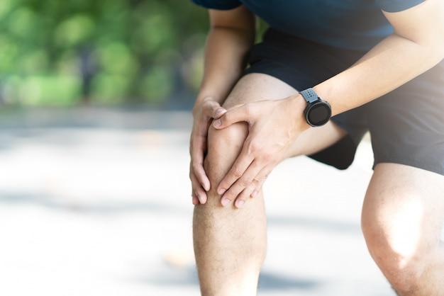 Молодой азиатский sporty человек держа боль колена в идущем общественном природном парке Premium Фотографии