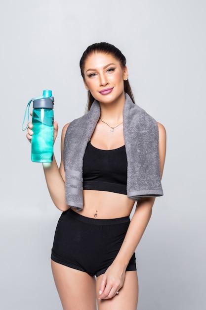 Красивая sporty кавказская женщина держа стекло воды изолированный Бесплатные Фотографии