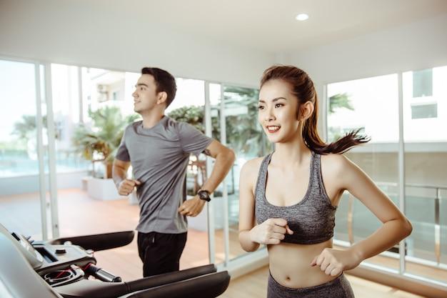 Молодые азиатские sporty женщины бегут на машине в центре спортзала Premium Фотографии