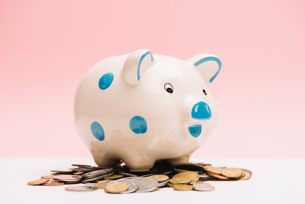 Spotted ceramic piggybank over coins Free Photo