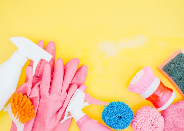 Spray bottle; brush; sponge and pink gloves on yellow backdrop Free Photo