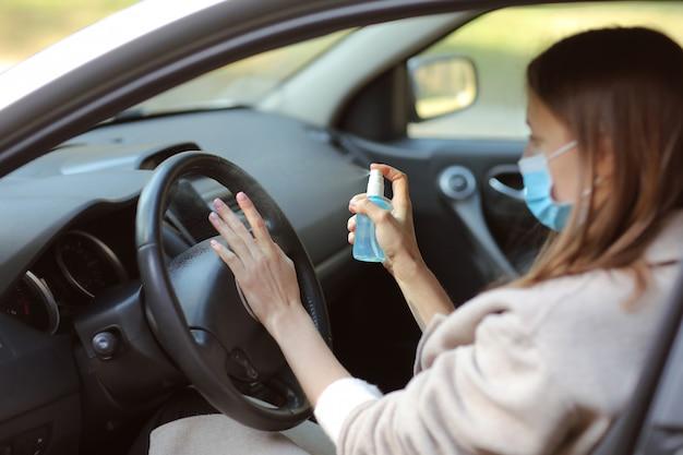 抗菌消毒スプレーを手に車にスプレー、感染管理のコンセプト。コロナウイルスを防ぐための消毒剤、covid-19。スプレー・ボトル。車を運転して医療用防護マスクを着ている若い女性。 Premium写真