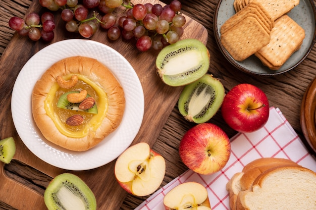 Spread the bread with jam and place it with kiwi and grapes Free Photo