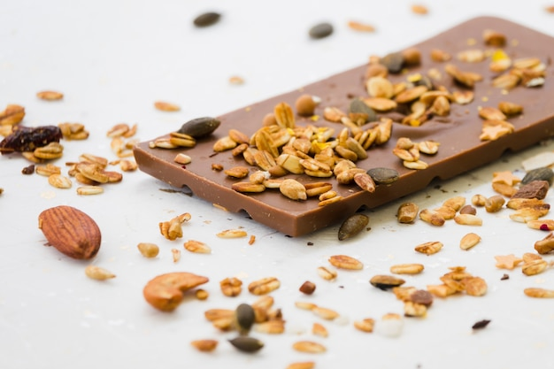 Spread dried fruits on chocolate bar against white backdrop Free Photo