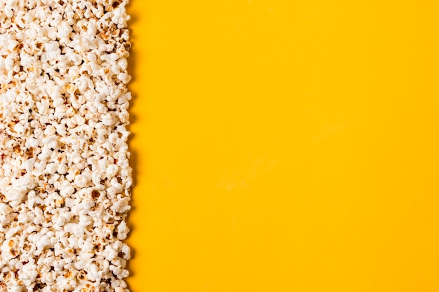 Spread popcorns on yellow background Free Photo