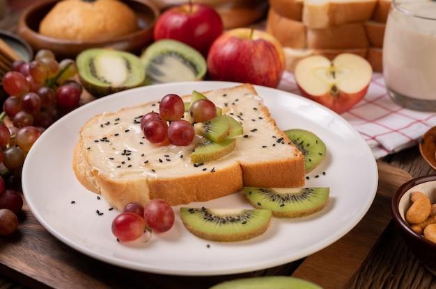 ジャムでパンを広げ、白い皿にキウイとブドウと一緒に置きます 無料写真