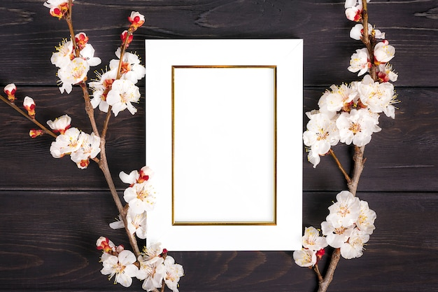 Sprigs of the apricot tree with flowers and white photo frame on wooden background. Premium Photo