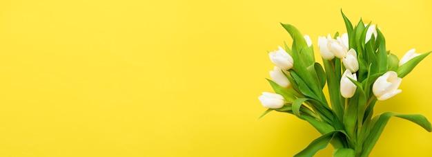 春のバナー黄色の照明の背景に白いチューリップの花束。イースターと春のグリーティングカード Premium写真
