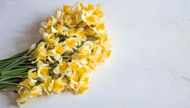 春に咲く、明るい木製の背景に黄色い水仙。バックの背景。 無料写真