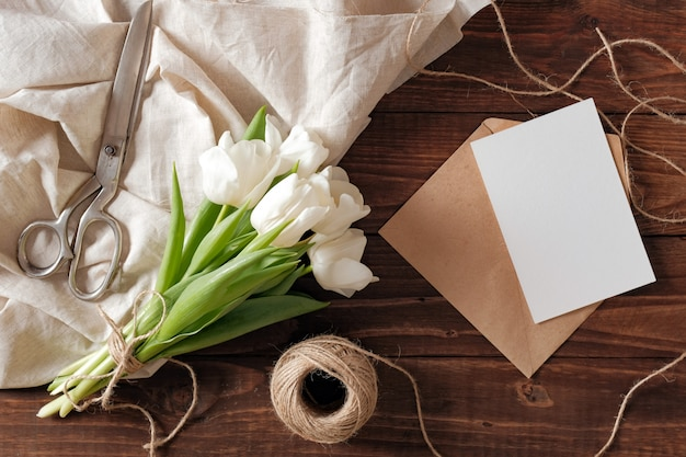 Spring bouquet of white tulip flowers, blank paper card, scissors, twine on rustic wooden desk. Premium Photo
