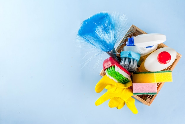 Spring cleaning concept with supplies, house cleaning products pile. household chore concept, on light blue background copy space top view Premium Photo