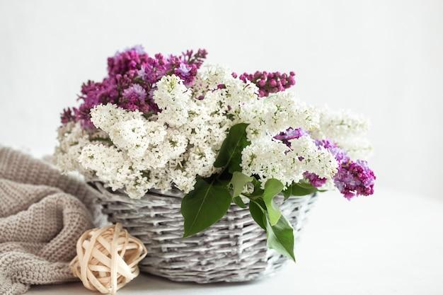 籐のかごに色付きのライラックの花が入った春の構図。 無料写真