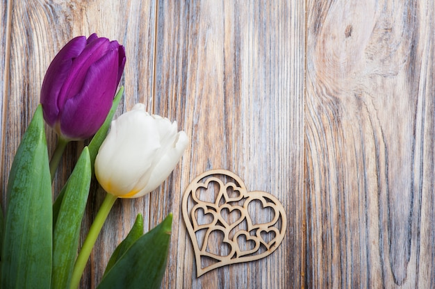 Spring composition with tulips and wooden heart Premium Photo