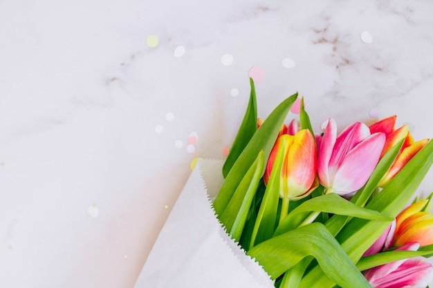 Spring concept. golden star decorations, vibrant confetti and pink and red tulips on marble background. copy space, flat lay. Premium Photo