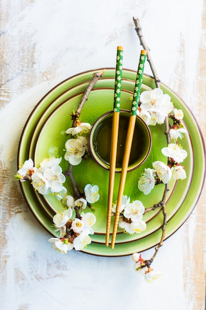 Spring concept with cup of green tea and peach blooming branch Premium Photo
