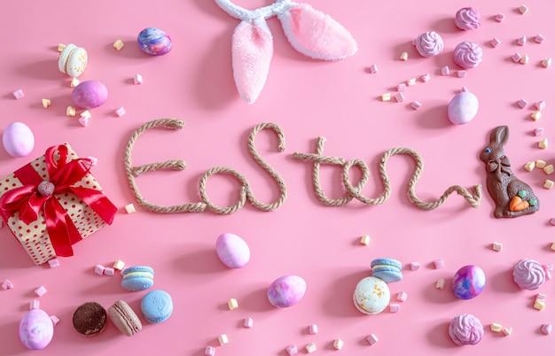 春のイースターお祝い。イースター装飾のアイテムとピンクのイースター創造的な碑文。 無料写真