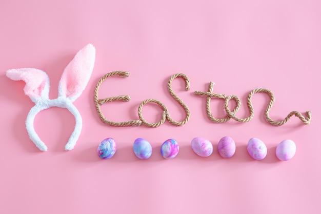 Primavera pasqua festosa iscrizione creativa di pasqua sul rosa con elementi di decorazioni pasquali. Foto Gratuite