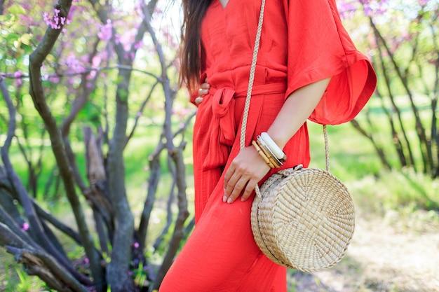 Look alla moda primaverile, donna con borsa di paglia alla moda bohémien bali in rattan alla moda e indossa un abito boho corallo. Foto Gratuite