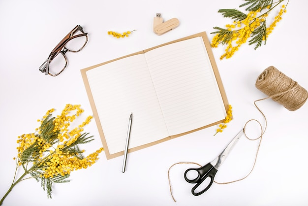 Spring festive set decorated with flowers mimosa notepad flash drive glasses scissors rope Free Photo