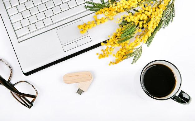 Spring festive set with flowers and a laptop on a white background Free Photo