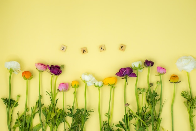 Spring flatlay concept background with flowers and sale wooden word Premium Photo