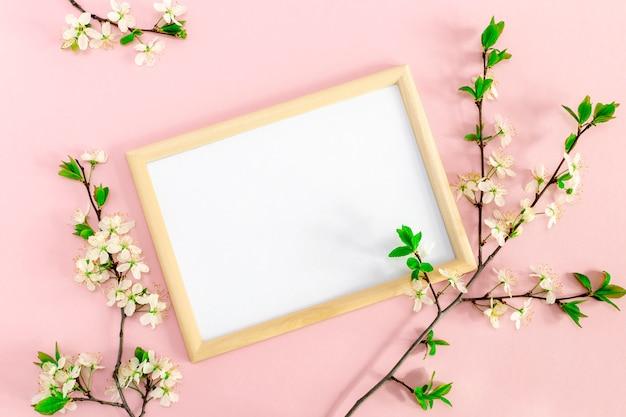 Cabang bunga musim semi dengan bunga sakura di sekitar bingkai foto.  kosong putih untuk teks dan kutipan inspiratif atau motivasi dengan latar belakang pink lembut.  mockup, tampilan atas datar, ruang salin.  Foto Premium