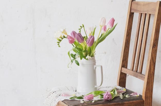 背景の古い白い壁の古い椅子に春の花 Premium写真
