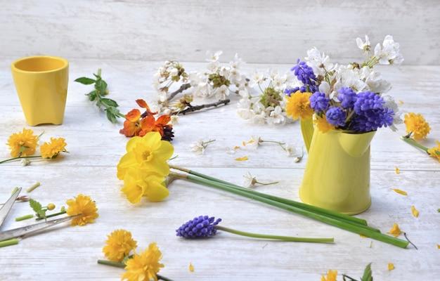 Весенние цветы собраны из сада и расположены на столе, чтобы сделать букет в домашних условиях Premium Фотографии