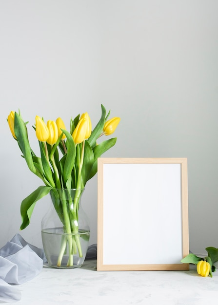 Spring flowers in vase with frame beside Free Photo