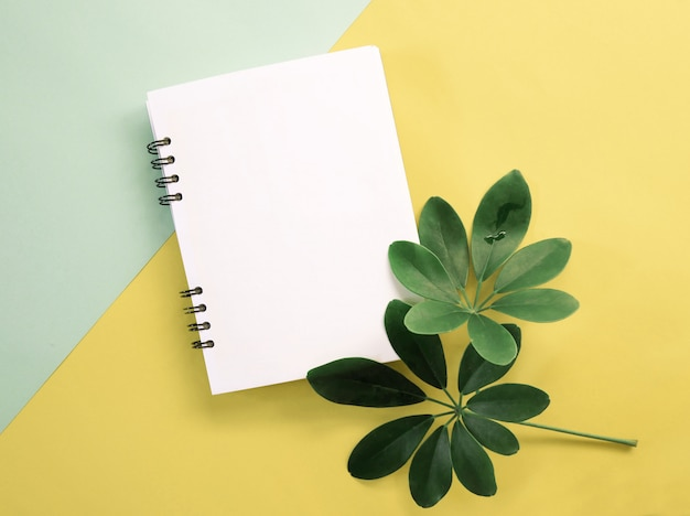 Spring green leaves with blank notebook Premium Photo
