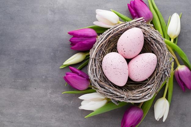 春のグリーティングカード。巣の中のイースターエッグ。春の花のチューリップ。 Premium写真