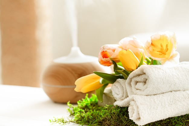 Spring spa still life with the aroma of a modern oil diffuser with towels. Free Photo