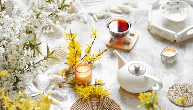 Primavera ancora in vita con una tazza di tè e fiori. sfondo chiaro, casa fiorita e accogliente. Foto Gratuite