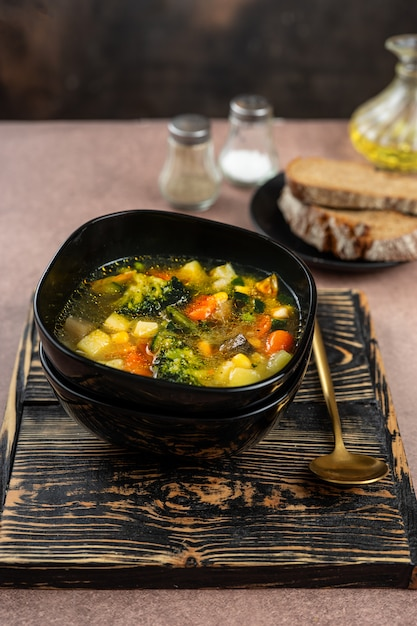 Spring vegetable soup in a black bowl Premium Photo