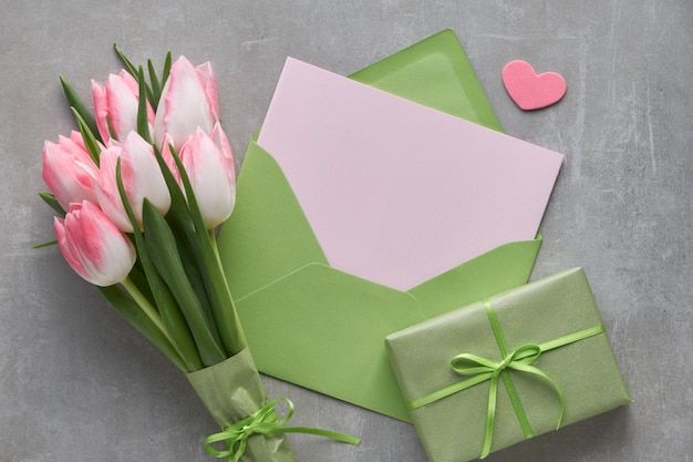 Springtime blue  background with pink tulips, wrapped gift box and decorative hearts Premium Photo