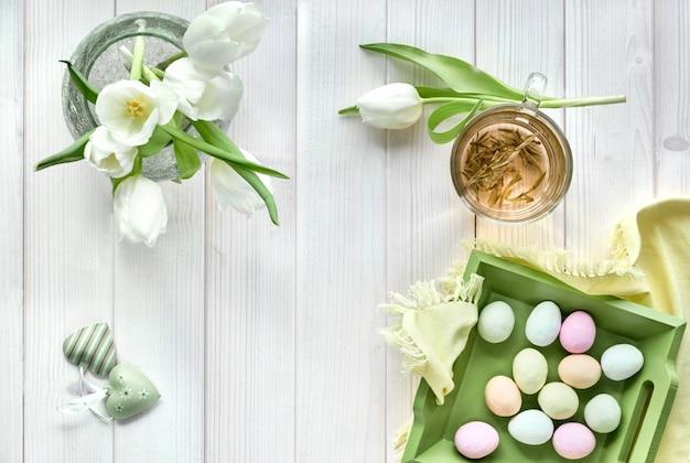 春のフラットは、パステルカラー、白いチューリップ、緑茶のカップ、明るい木の上の砂糖イースターエッグで横たわっていた Premium写真