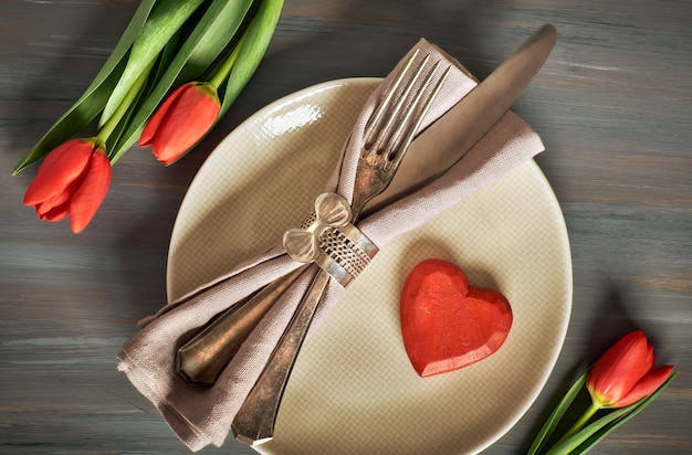 Springtime menu concept with fresh tulips and heart decoration on gray wood Premium Photo