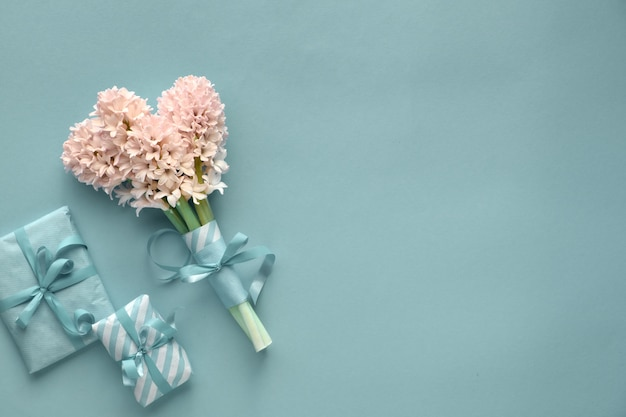 Springtime turquoise  with hyacinth and gift boxes wrapped in stripy paper on paper background with copy-space Premium Photo